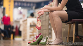 Woman sitting in shoe store. Hard choice. Close-up of young woman sitting in shoe store while different shoes laying near her royalty free stock images