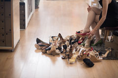 Woman sitting in shoe store. Hard choice. Close-up of young woman sitting in shoe store while different shoes laying near her Stock Photography