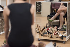 Woman sitting in shoe store. Hard choice. Close-up of young woman sitting in shoe store while different shoes laying near her Stock Image
