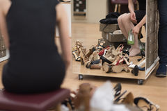 Woman sitting in shoe store. Hard choice. Close-up of young woman sitting in shoe store while different shoes laying near her Royalty Free Stock Image