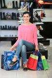 Woman sitting with shopping bags Stock Images