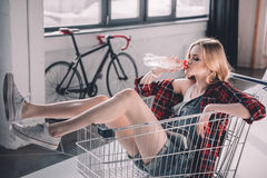 Woman sitting in shopping cart and drinking water. Young woman sitting in shopping cart and drinking water Stock Images