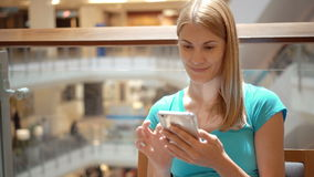 Woman sitting in shopping mall square using smartphone, browsing, reading news, chatting with friends. Young smiling woman sitting in shopping center cafe using stock video