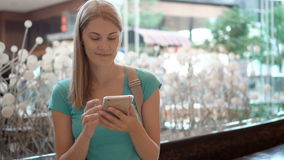 Woman sitting in shopping mall square using smartphone, browsing, reading news, chatting with friends. Young smiling woman sitting in shopping mall plaza using stock footage