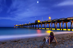 Woman sitting on shore at night Royalty Free Stock Photography