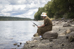 Woman sitting on the shore on a rock fishing. Stock Photo
