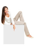Woman sitting on / showing sign Royalty Free Stock Photography