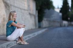 Woman sitting on the sidewalk Stock Photos