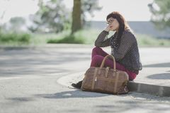Woman sitting on a sidewalk waiting for a bus Stock Photos