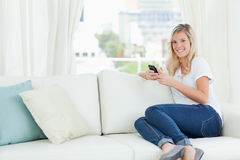 A woman sitting sideways on the couch as she uses her phone and Royalty Free Stock Image