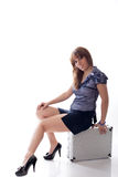 Woman is sitting on silver  case Stock Photography