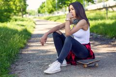 Woman sitting on skateboard. Outdoors, urban lifestyle stock photo