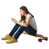 Woman sitting on skateboard and using smart phone Stock Image