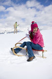 Woman sitting on sled having snowball fight with boyfriend royalty free stock photo