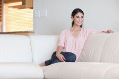 Woman sitting on a sofa Stock Image
