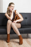 Woman sitting on sofa Stock Images