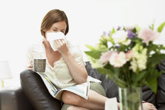 Woman Sitting On Sofa Blowing Nose Royalty Free Stock Images