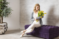 Woman sitting on the sofa with a bouquet of yellow tulips Stock Image