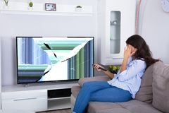 Woman Sitting On Sofa With Broken Television stock photography
