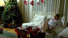 Woman Sitting On A Sofa At Christmas Evening. stock video