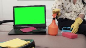 Woman sitting on sofa with cleaning agents near laptop with green screen stock footage