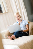 Woman sitting on the sofa with computer Stock Photography