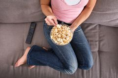 Woman Sitting On Sofa Eating Popcorn royalty free stock photos