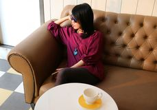Woman sitting on a sofa with an empty coffee cup on the table stock images