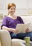 Woman sitting on sofa enjoying reading book. Relaxed woman sitting on sofa enjoying reading book royalty free stock photos