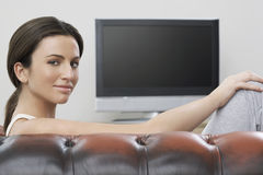 Woman Sitting On Sofa With Flat Screen TV In Background Royalty Free Stock Images