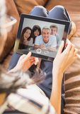 Woman sitting on sofa having video call with family on digital tablet. At home Stock Image