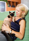 Woman sitting on sofa with her cat Stock Images