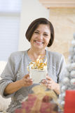 Woman Sitting On Sofa Holding A Christmas Gift Stock Image