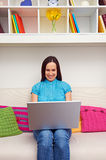 Woman sitting on sofa and holding the laptop Stock Photo