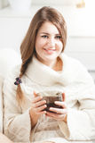 Woman sitting on sofa and holding tea cup Stock Photography