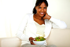 Woman sitting on sofa and holding vegetable salad Stock Photos