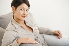 Woman sitting on sofa at home stock photography