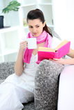 Woman sitting on sofa at home stock image