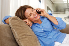 Woman sitting on sofa at home with mobile phone Royalty Free Stock Images