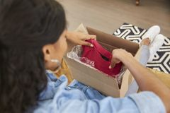 Woman Sitting On Sofa At Home Opening Online Clothing Purchase Stock Photography