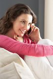 Woman Sitting On Sofa At Home Talking On Phone Stock Images