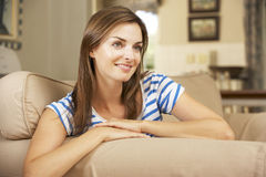 Woman Sitting On Sofa At Home Watching TV Stock Photo