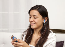 Woman sitting on sofa and listening to music Stock Image