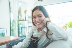 Woman sitting on sofa in living room and smiling Royalty Free Stock Image