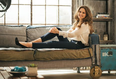 Woman sitting on sofa in loft apartment Royalty Free Stock Image