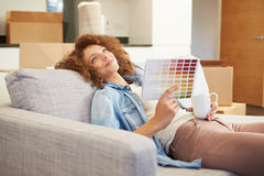 Woman Sitting On Sofa Looking At Paint Charts. And Holding Hot Drink Thinking royalty free stock photos