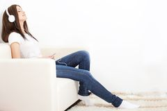 Woman sitting on sofa and looking at player Stock Images