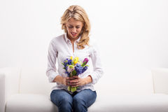 Woman sitting on sofa and looking at pretty flowers Stock Photos