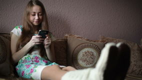 Woman sitting on sofa and looking at smartphone stock video