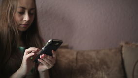 Woman sitting on sofa and looking at smartphone stock video footage